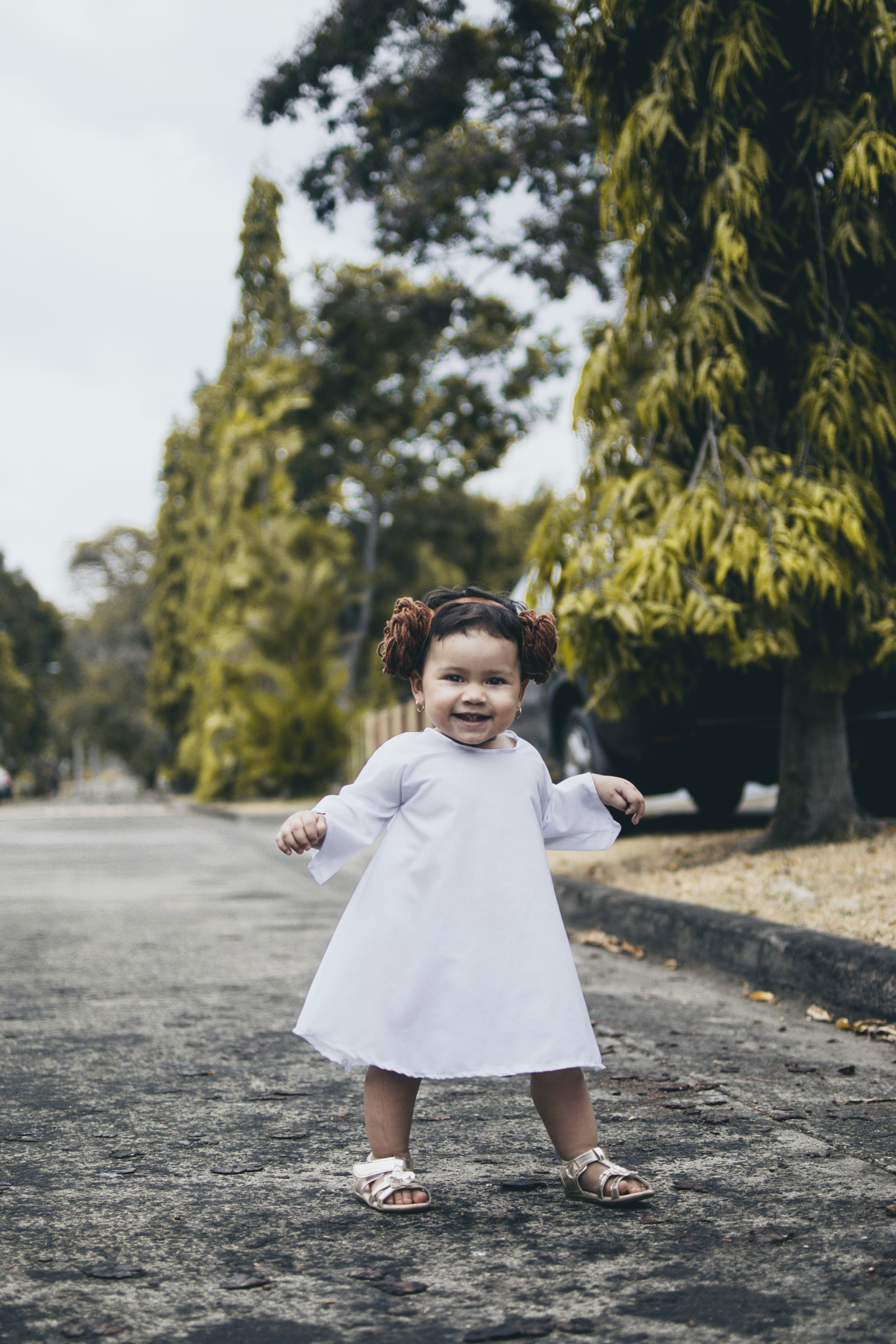 Smiling Baby Girl Wearing White Dress Standing on Road
