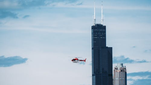 Time Lapse Photography of Helicopter With High-rise Building Background