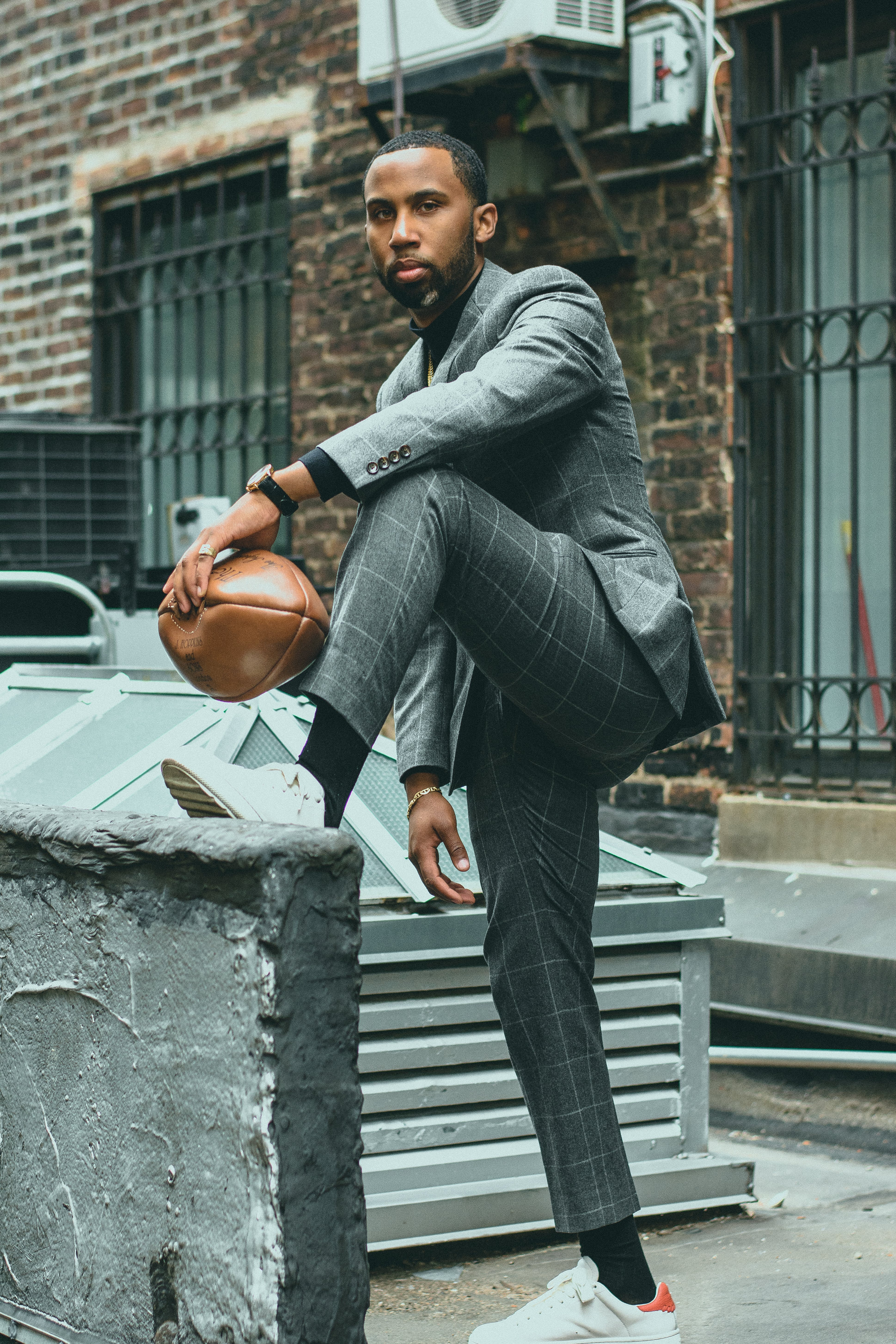 Men's Gray Suit Holding Brown Football