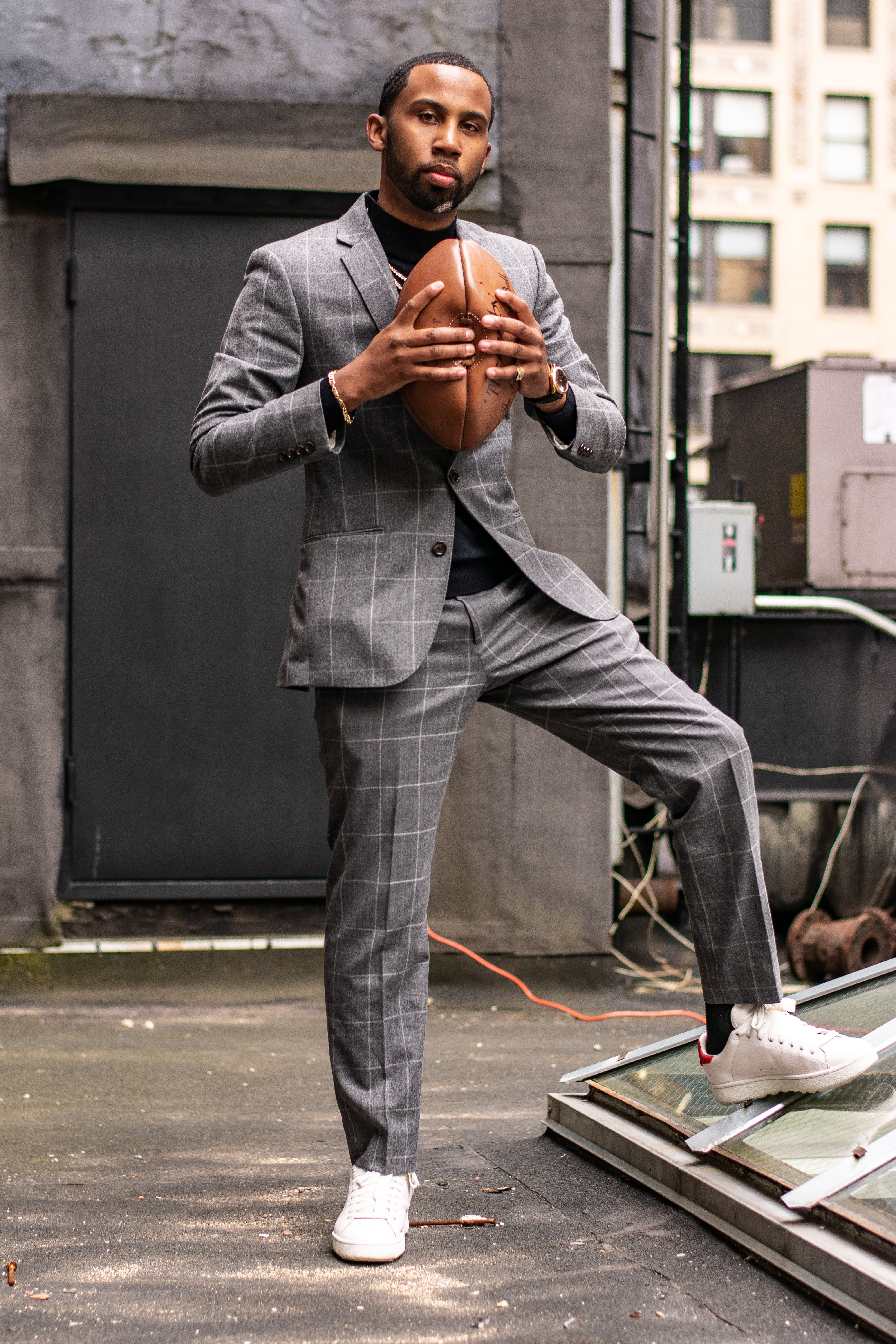 Man Wearing Grey Tuxedo Holding American Football