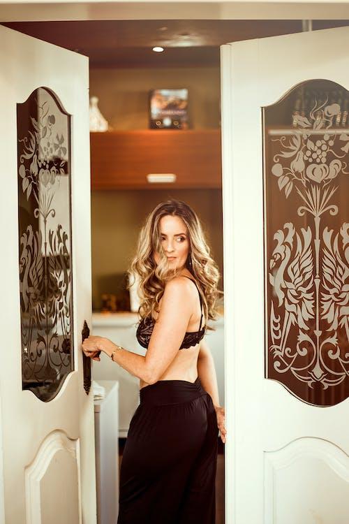 Женщина, стоящая в открытой двери, откинувшись назад