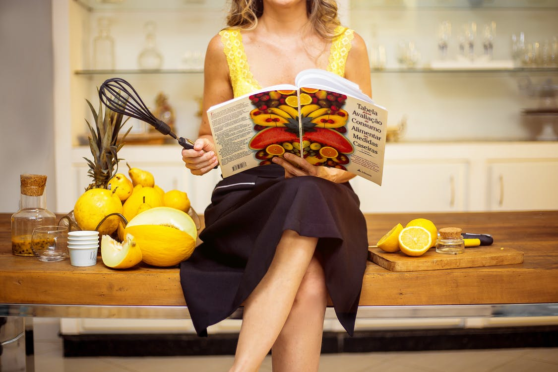 Woman Sitting on Table Holding Black Whisk and Cookbook