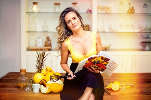 Woman Sitting on Wooden Table Inside Kitchen