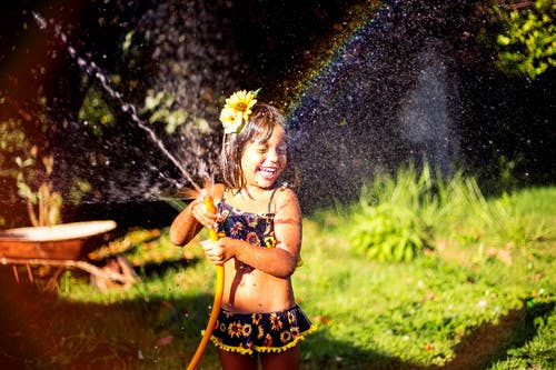 Smiling Girl Playing With Water Hose