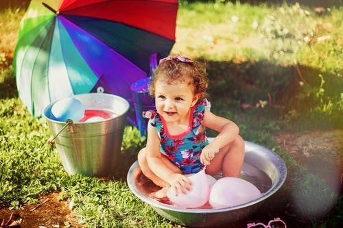 Smiling Girl Sitting on Gray Stainless Steel Basin Playing With Pink Balloons