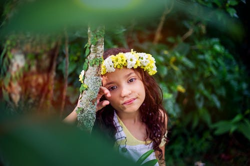 Girl in White and Yellow Tank Top and Yellow and White Floral Headdress Leaning on Tree Trunk