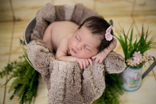 Baby Sleeping On Brown Textile