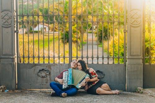 Mulher E Homem Tocando Instrumento Musical Perto Do Portão