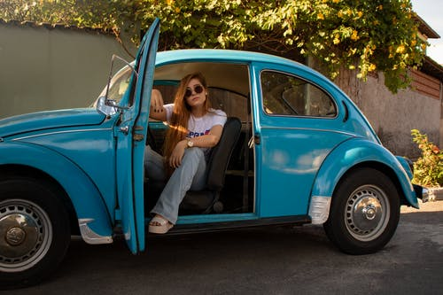 Woman Wearing White Shirt Sitting Inside Blue Volkswagen Beetle