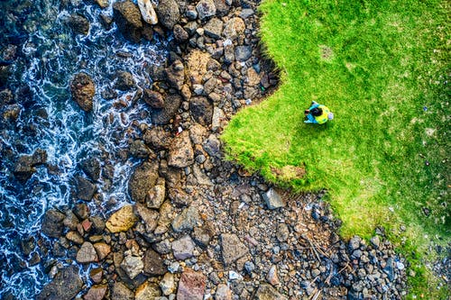 Aerial View Photography of Person Sitting on Green Grass