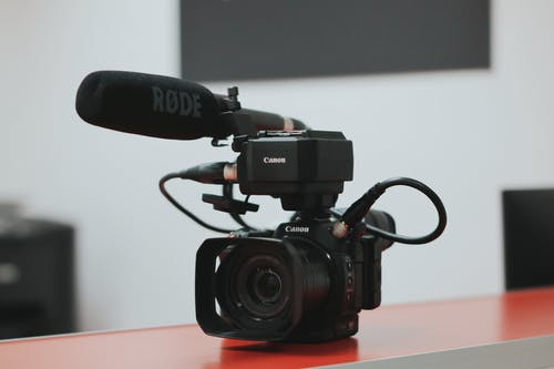 Black Canon Video Camera With Microphone on Desk