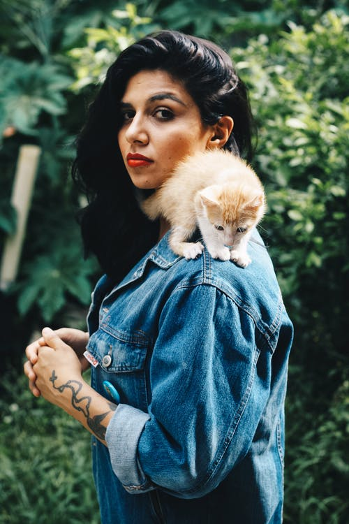 Standing Woman With Orange Tabby Kitten on Her Shoulder