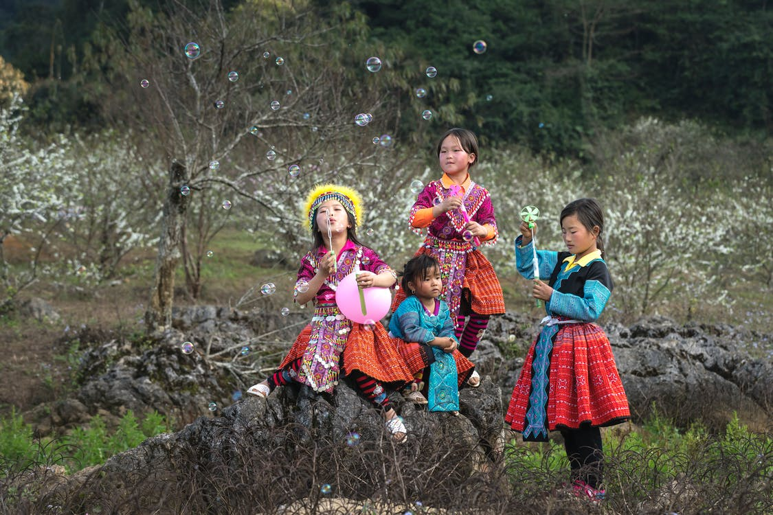 Four Girls in Tribal Dresses Near Grey Rocks
