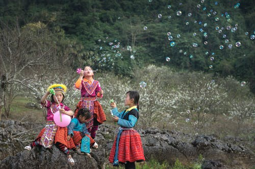 Four Girls Playing Bubbles on the Field