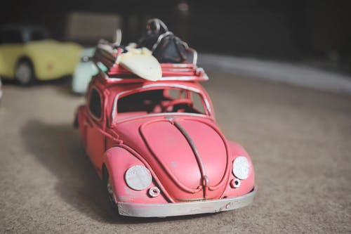 Pink Volkswagen Beetle Scale Model on Brown Surface