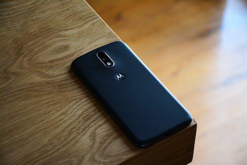 Black Motorola Smartphone on Top of Brown Wooden Table