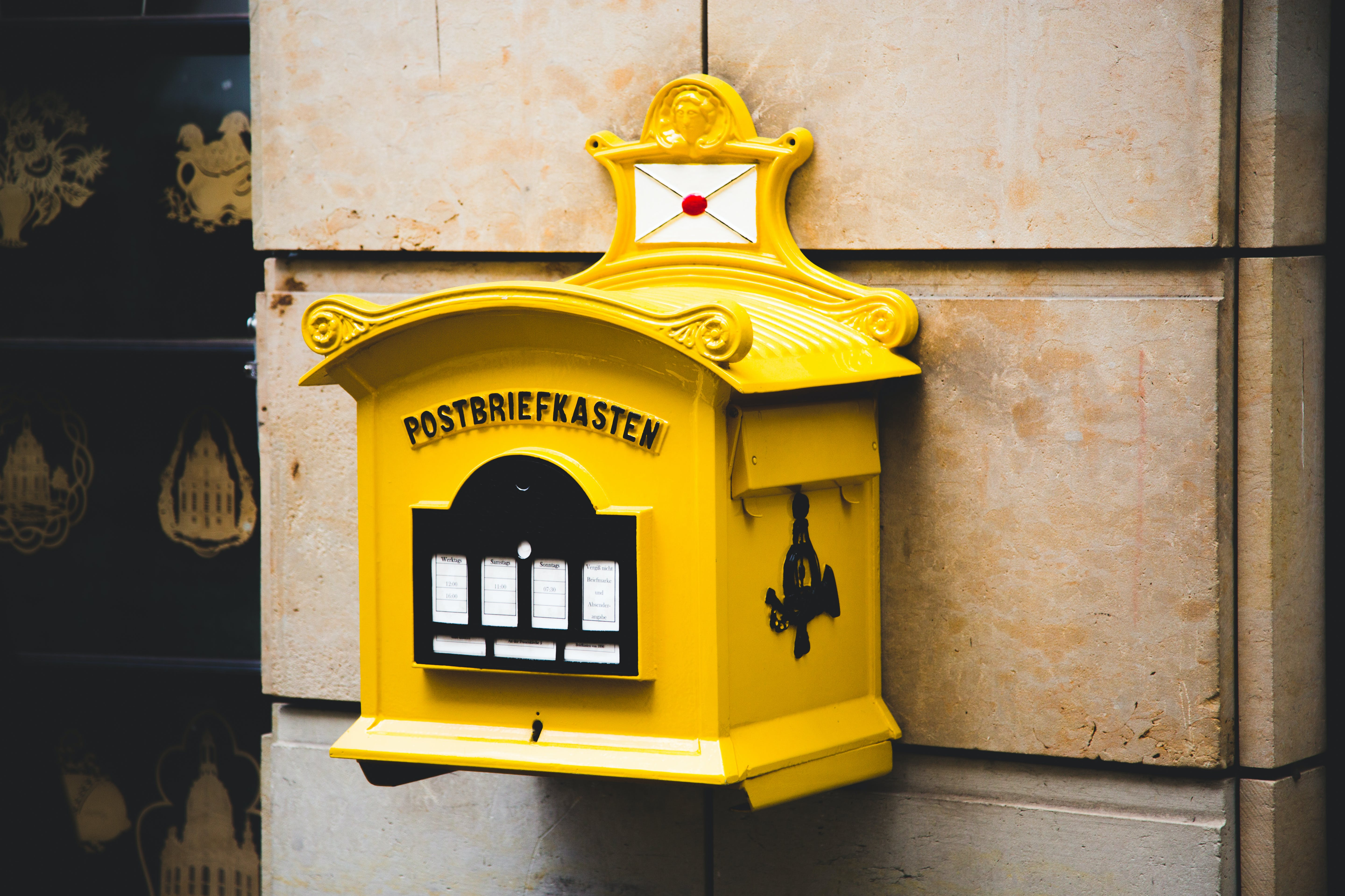Yellow Postbriefkasten Floating Mailbox on Brown Concrete Wall