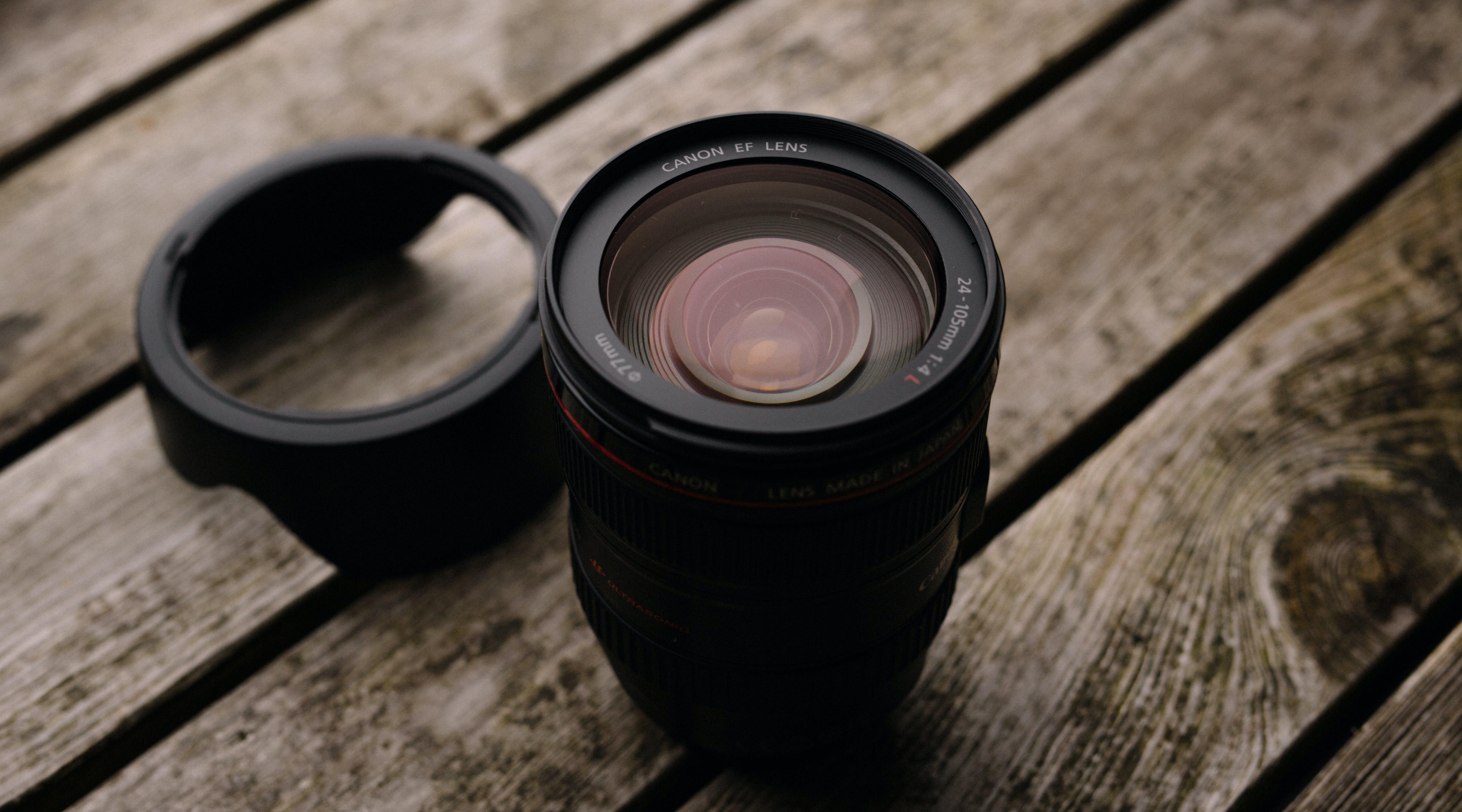 Black Dslr Camera Lens With Lid on Wooden Platform