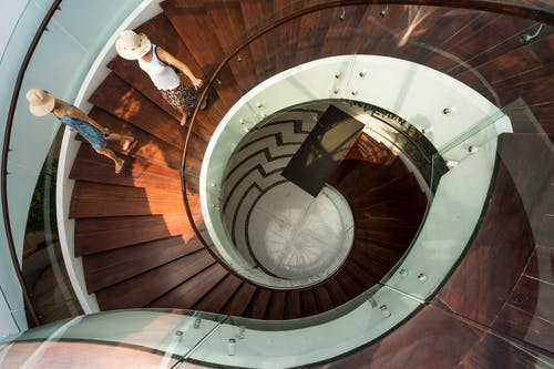 Two People Walking On Spiral Stairs