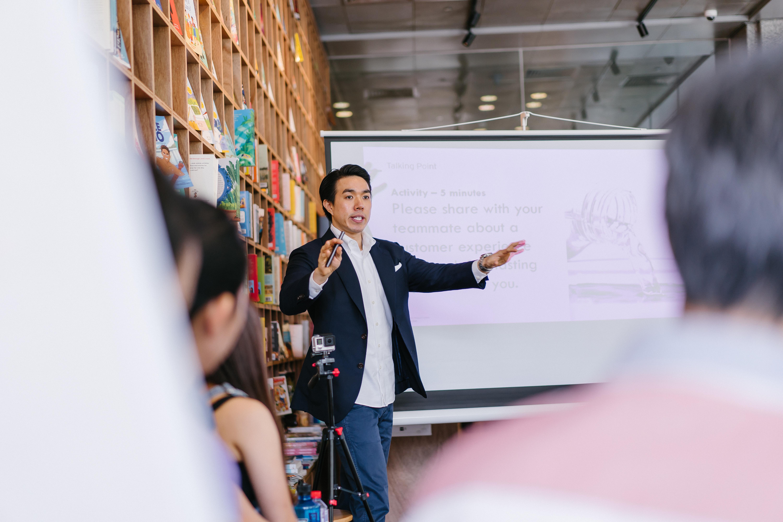 Homem de pé explicando, conversando com uma pequena plateia, para ilustrar o processo de mentoria aplicado pela we treinamento para crescimento profissional.