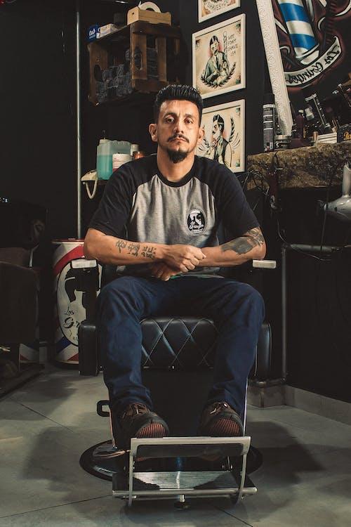 Man Sitting On Barber Chair Inside Room