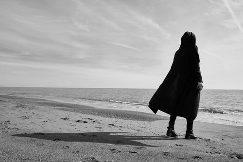 Grayscale Photo of Person Standing on Seashore