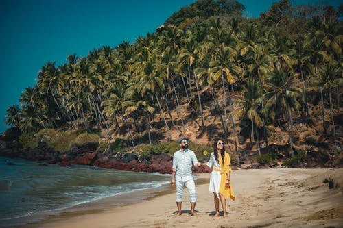 Man and Woman Standing on Seashore Near Mountain Covered With Coconut Trees