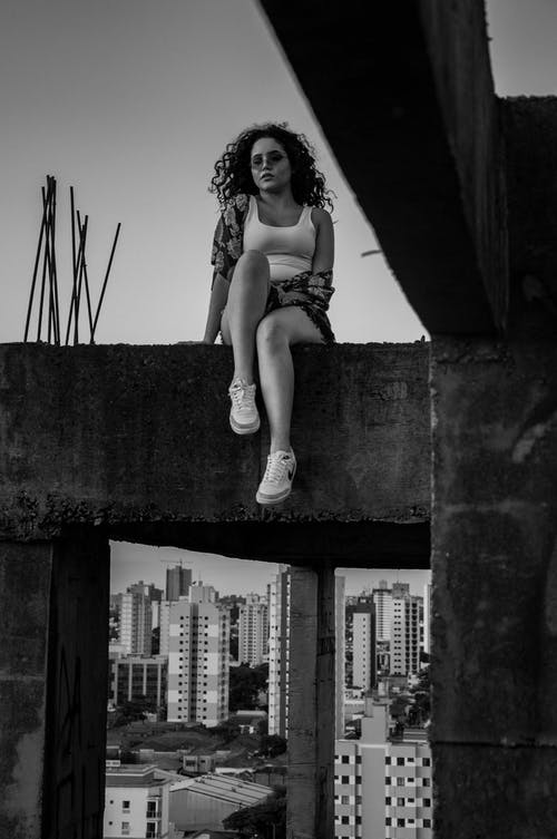 Woman Sitting on Concrete Structure