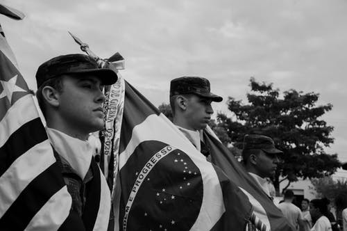 Monochrome Photo of Men Carrying Flags