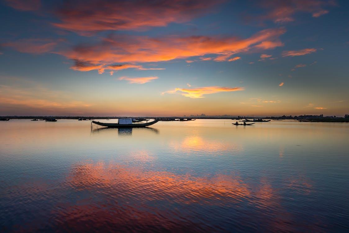 Motor Boats on Sea Under Orange and Blue Skeis
