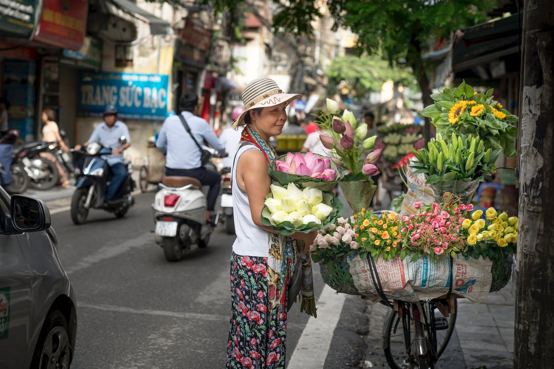 Woman Standing and Looking on Petaled Flowers on Street