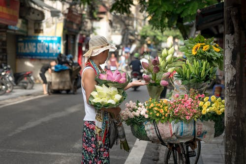 Woman Selling Flowers on Roadside