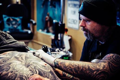 Man Doing Tattoo Inside Room