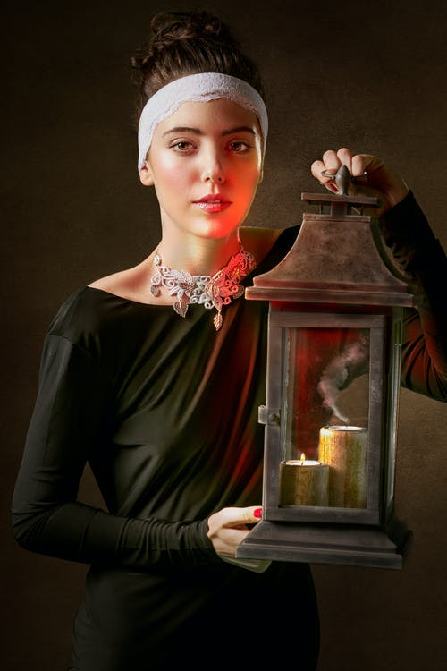 Woman in Green Long-sleeved Dress Holding Candle Holder