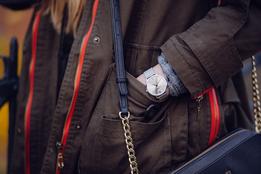 Woman Brown Coat Wearing Silver Analog Watch While Hand in Her Pocket