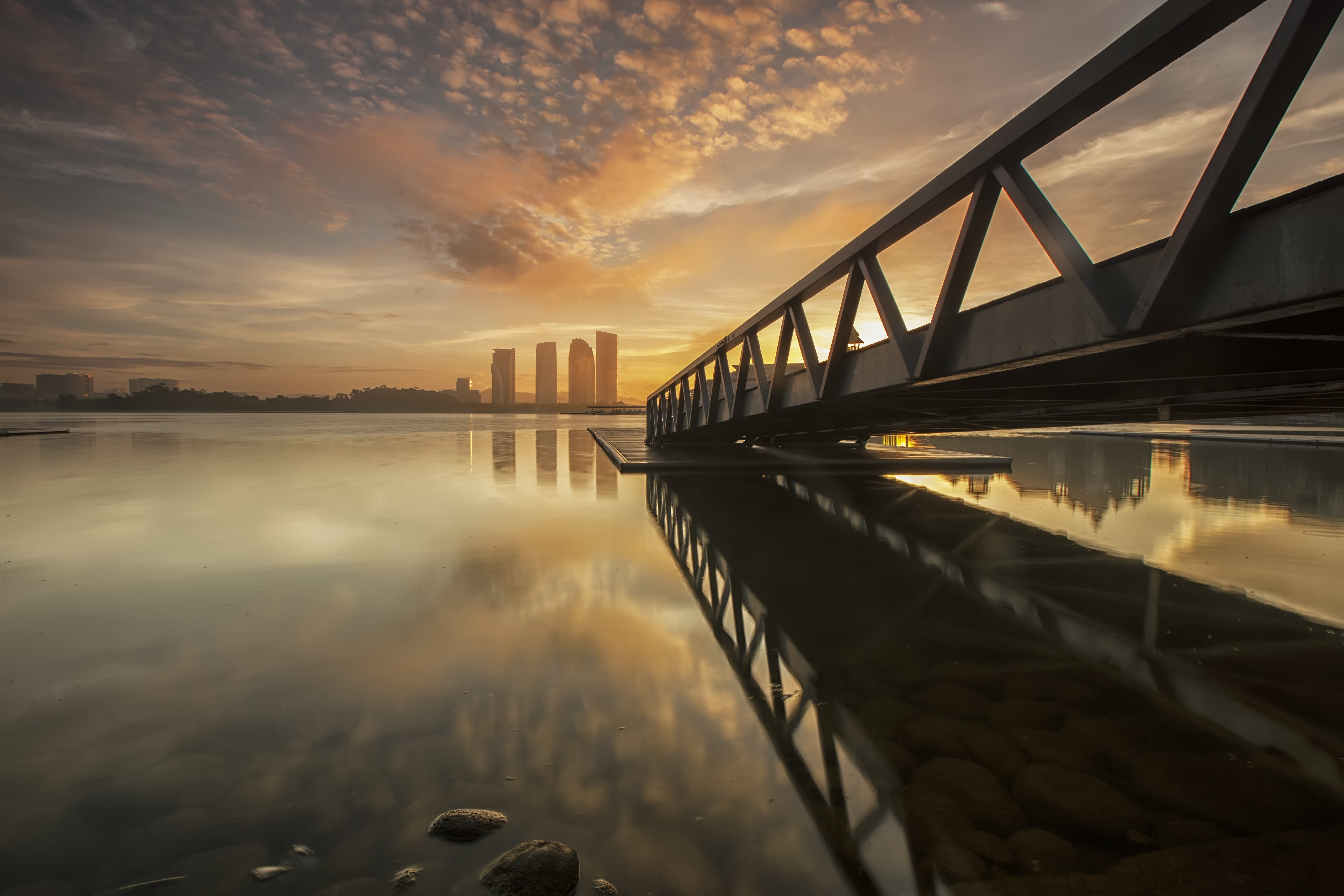 Bridge on Body of Water Near High-rise Building during Golden Hour