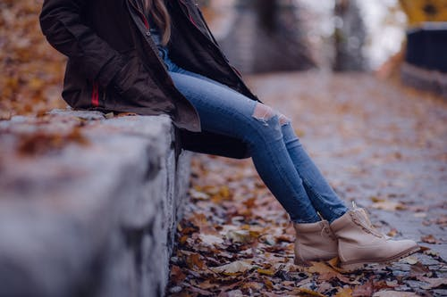Woman Wearing Black Jacket Blue Distressed Jeans and Brown Boots Sitting on Gray Concrete Barrier