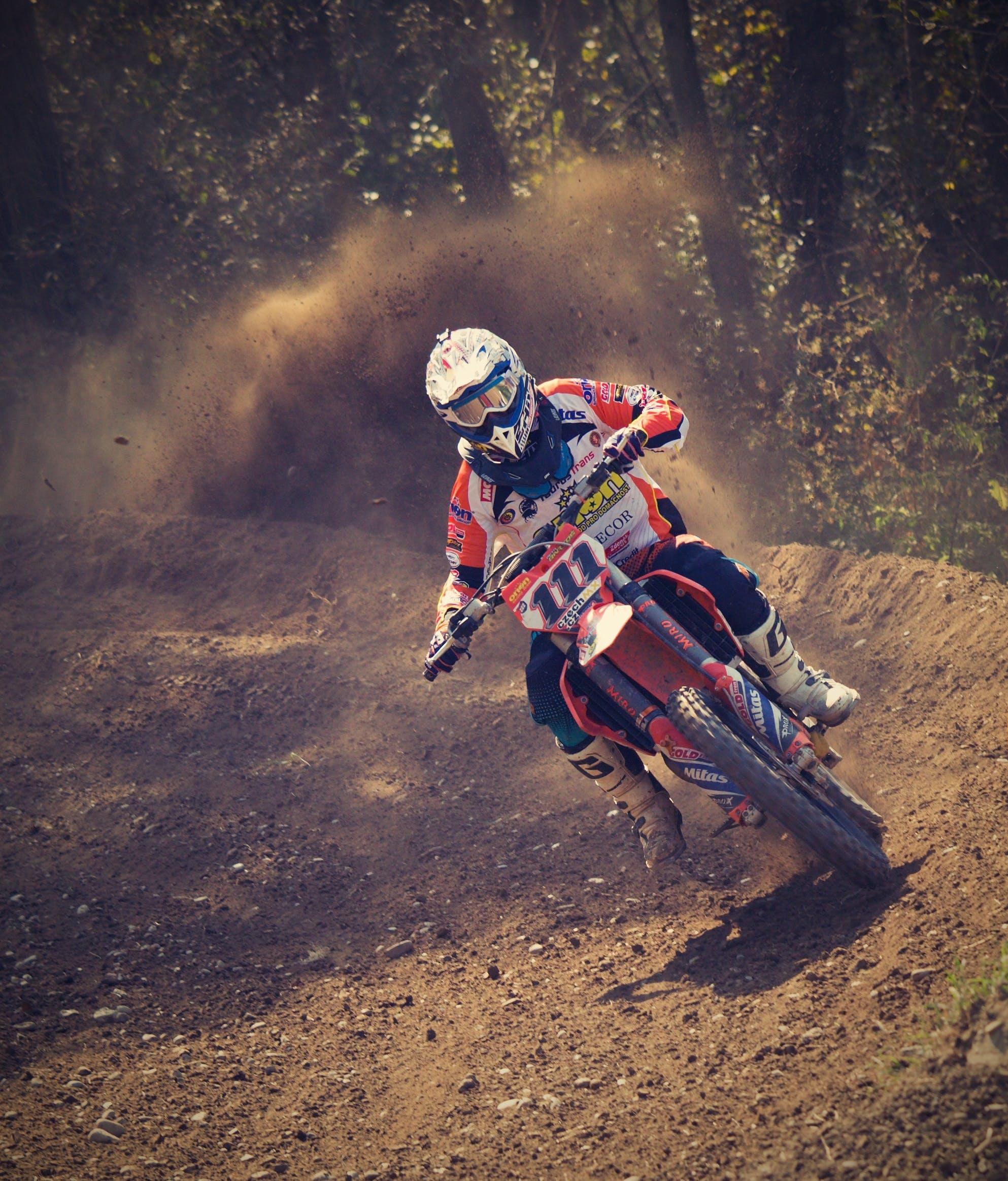 Man in White and Orange Motocross Overall Riding His Motocross Dirt Bike during Daytime