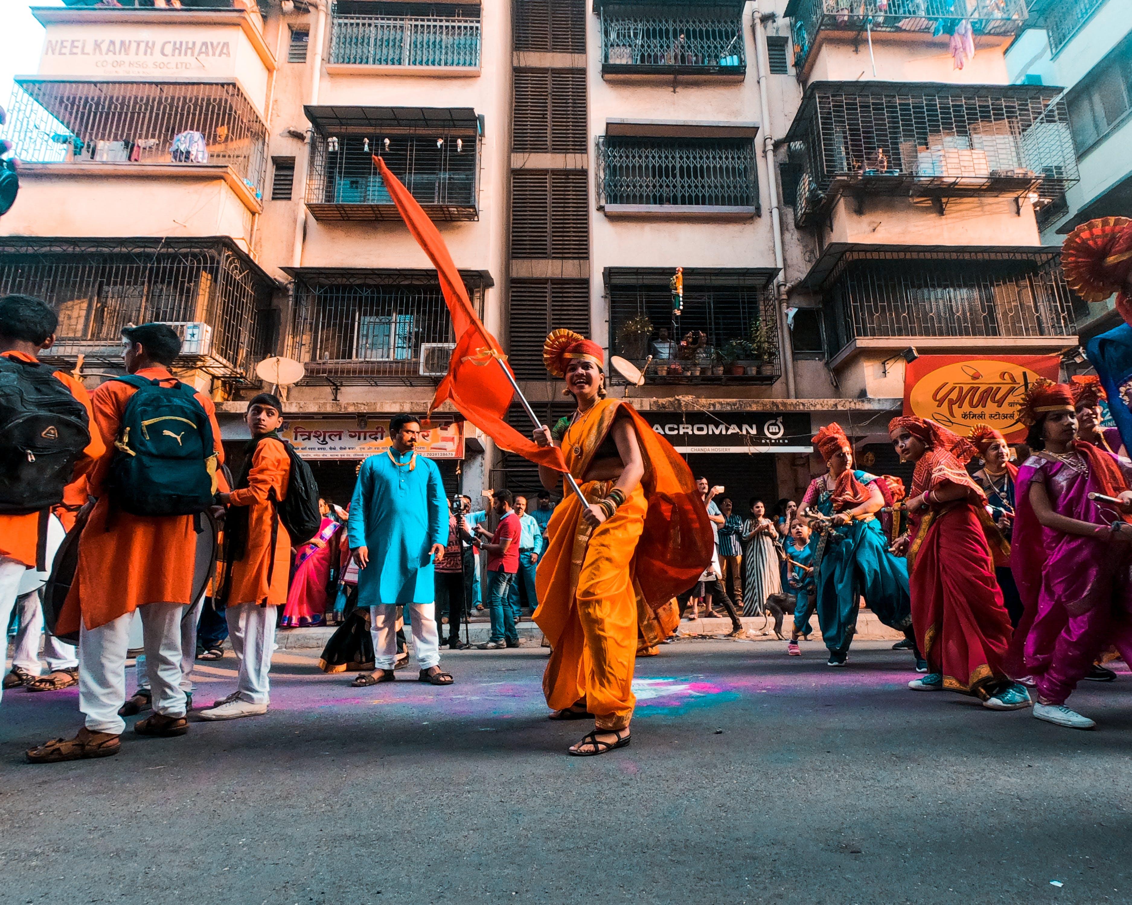 Man in Orange Skirt and Scarf Holding Orange Flag
