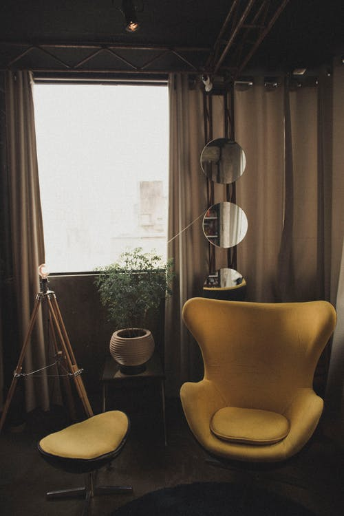 Yellow Chair Near Three Round Mirrors