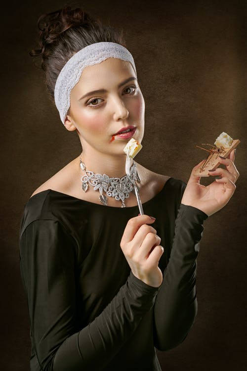 Photo of a Woman Holding Fork And Mousetrap