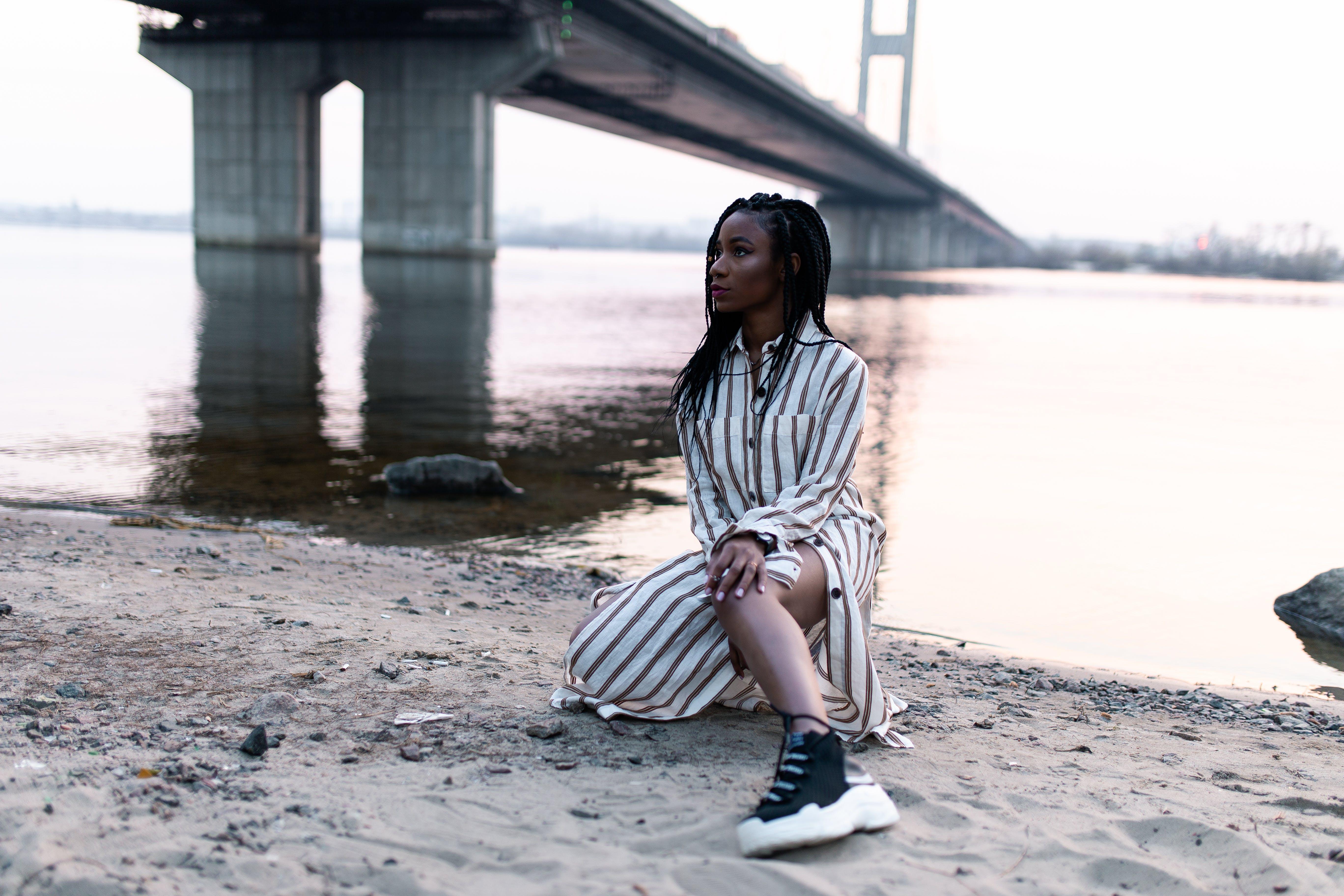 Woman Kneeling on Sand Near River and Bridge