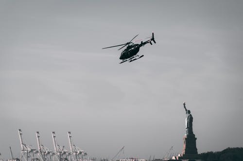 Photo of a Flying Helicopter Near Statue of Liberty