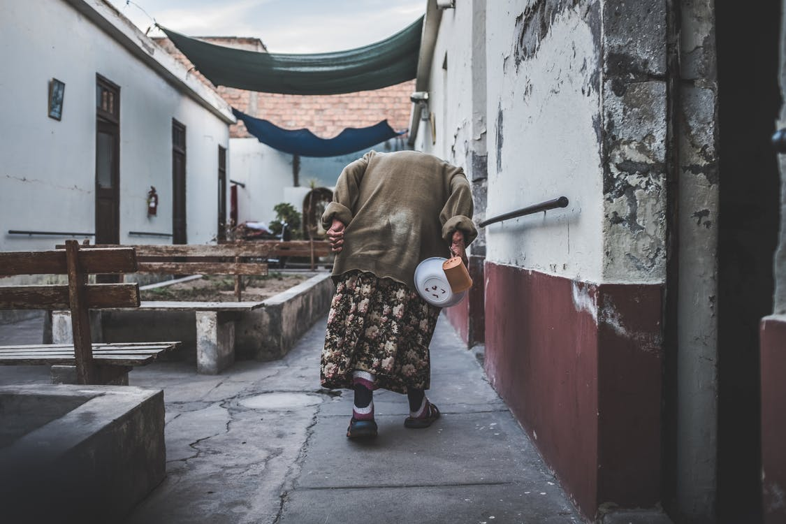 Old Person Walking Near Concrete Building