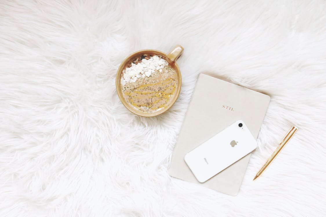 White Iphone, Gold-colored Pen, and Round Gold-colored Cup