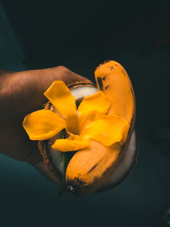 Yellow Petaled Flower and Banana In Coconut Shell