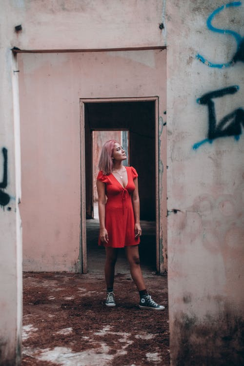 Woman in Red Dress Standing on Wrecked Building