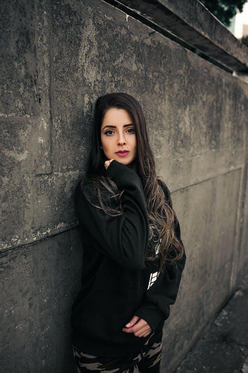 Woman Leaning on Wall Wearing Black Jacket