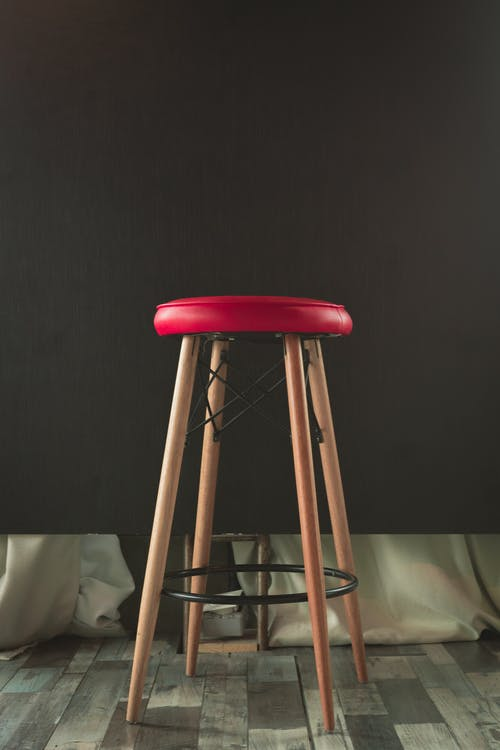 Round Red and Beige Bar Stool Near Wall
