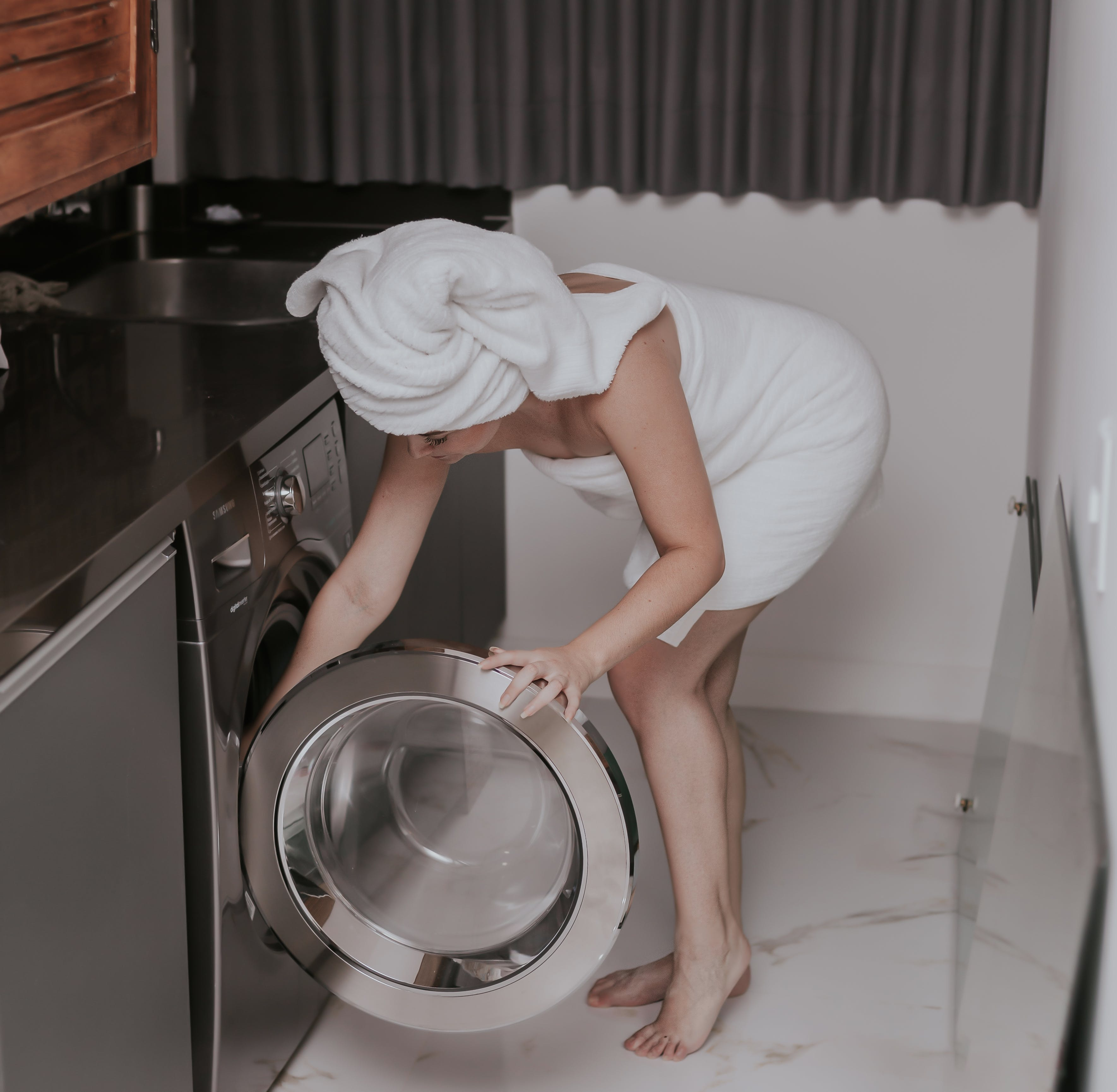 Woman Wearing White Towel While Washing Clothes
